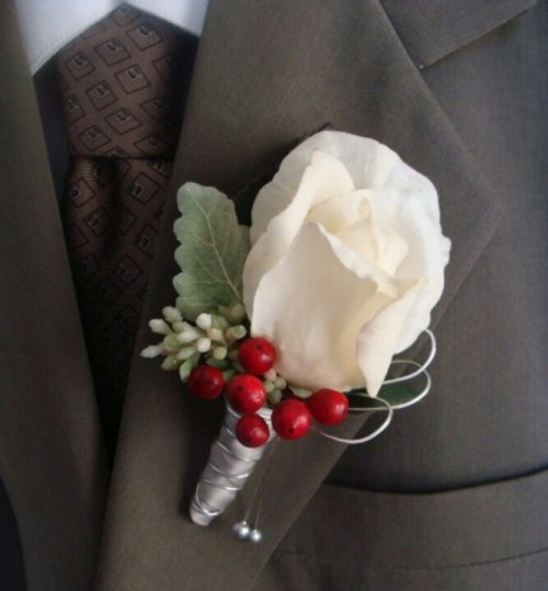 a white rose, pale leaves, berries boutonniere is a cute accessory for a winter groom