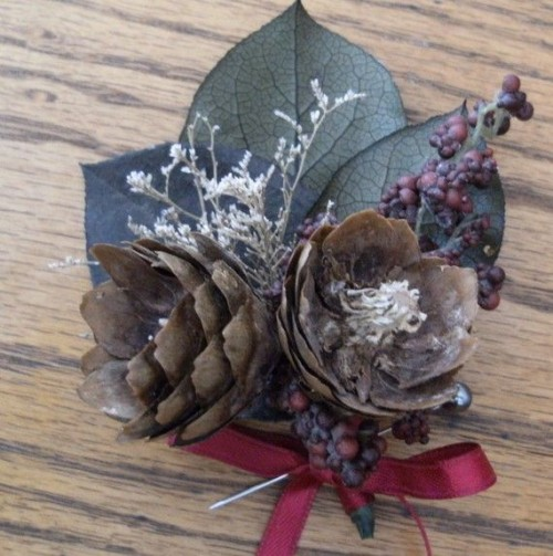 a rough winter boutonniere with pinecones, leaves, berries and dried herbs is a great accessory for a winter groom