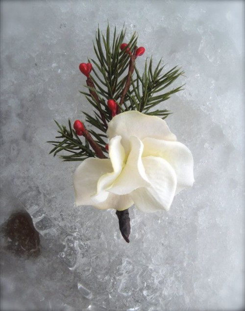 a winter wedding boutonniere of a white bloom, berries and fir branches is a cool and simple idea