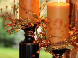 rust-colored candles covered with leaves and berries are great for decorating your fall wedding