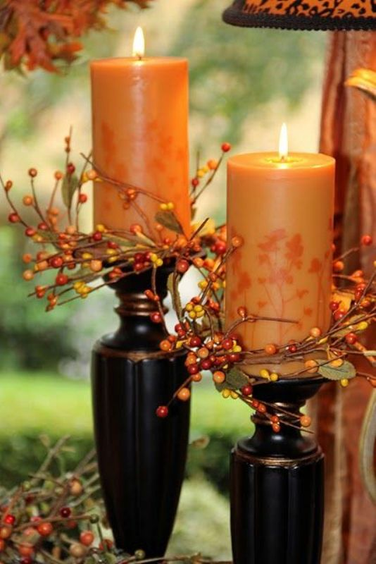 rust colored candles covered with leaves and berries are great for decorating your fall wedding