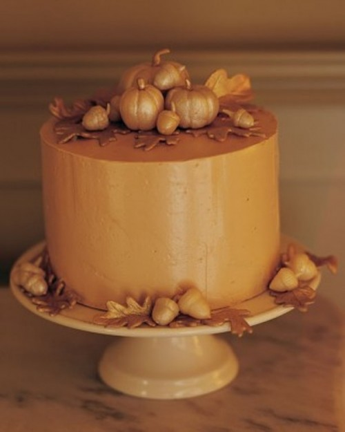 an amber buttercream wedding cake decorated with sugar leaves and mini pumpkins is great for a fall wedding