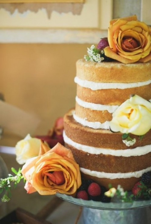 a naked wedding cake decorated with berries and amber and copper roses is great for a fall wedding