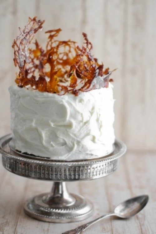 a white buttercream wedding cake with amber caramel shards on top is a very creative and cool idea for a modern fall wedding