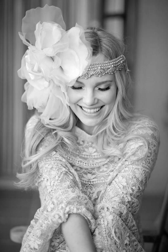 a sparkling rhinestone headpiece with an oversized fabric flower on one side for a glam boho bride