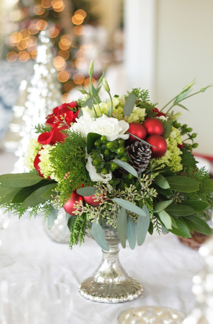 a chic and refined Christmas wedding centerpiece of a silver bowl, white and red blooms, pinecones and greenery is amazing