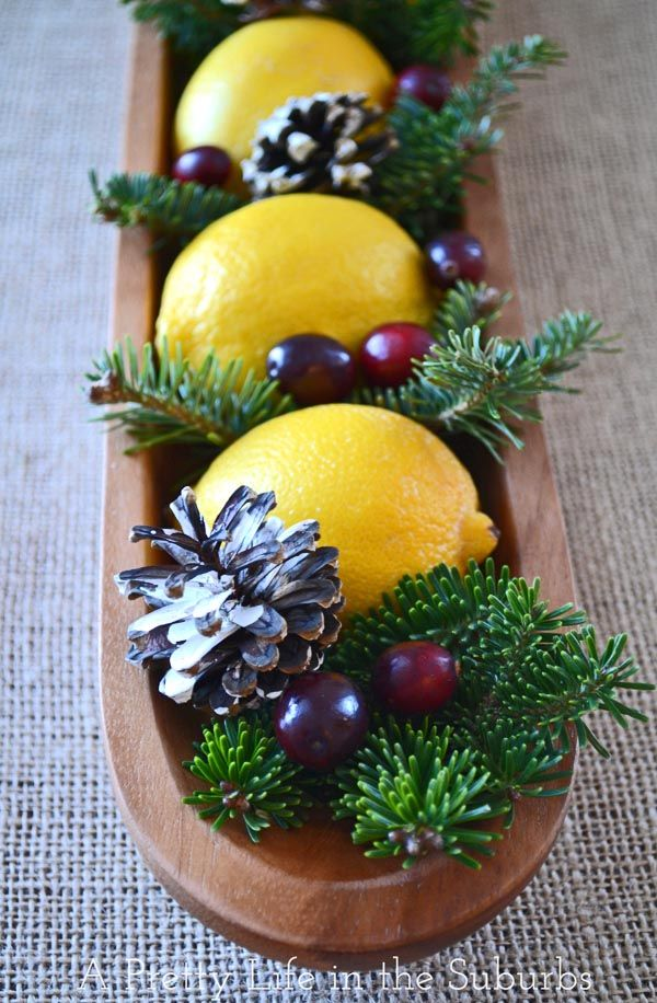 a cozy rustic Christmas wedding centerpiece of a long wooden bowl with pinecones, berries, fir branches and lemons is stunning