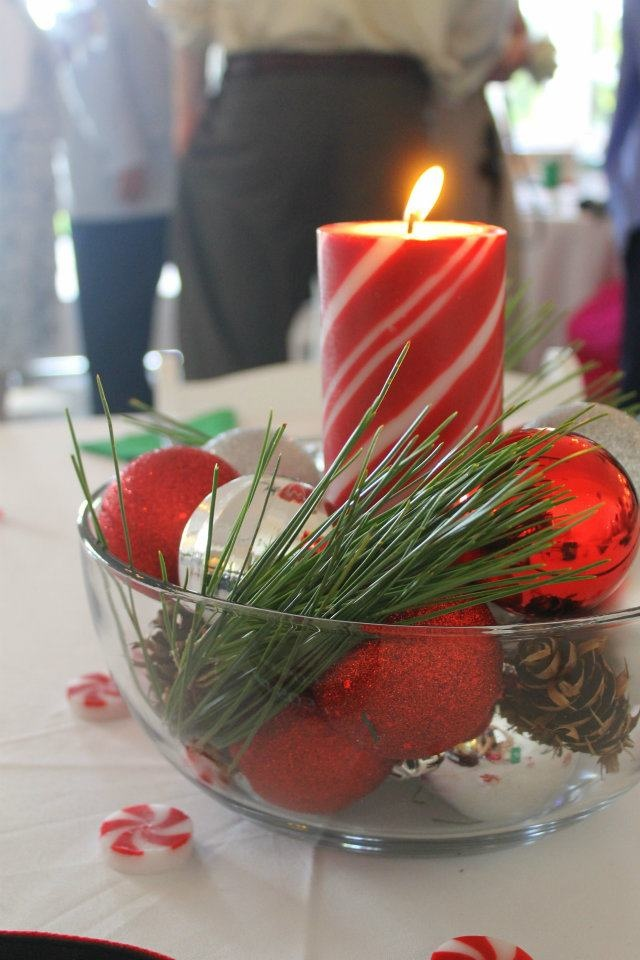 a simple Christmas wedding centerpiece of a wooden bowl with silver and red ornaments, a red candle and fir branches