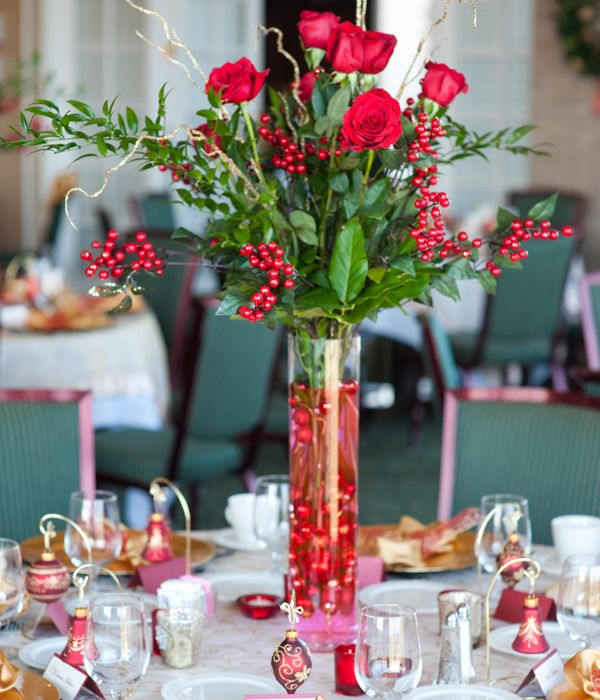 a bold Christmas centerpiece of a tall vase filled with red ornaments, greenery, berries, red roses, twigs is very elegant and chic