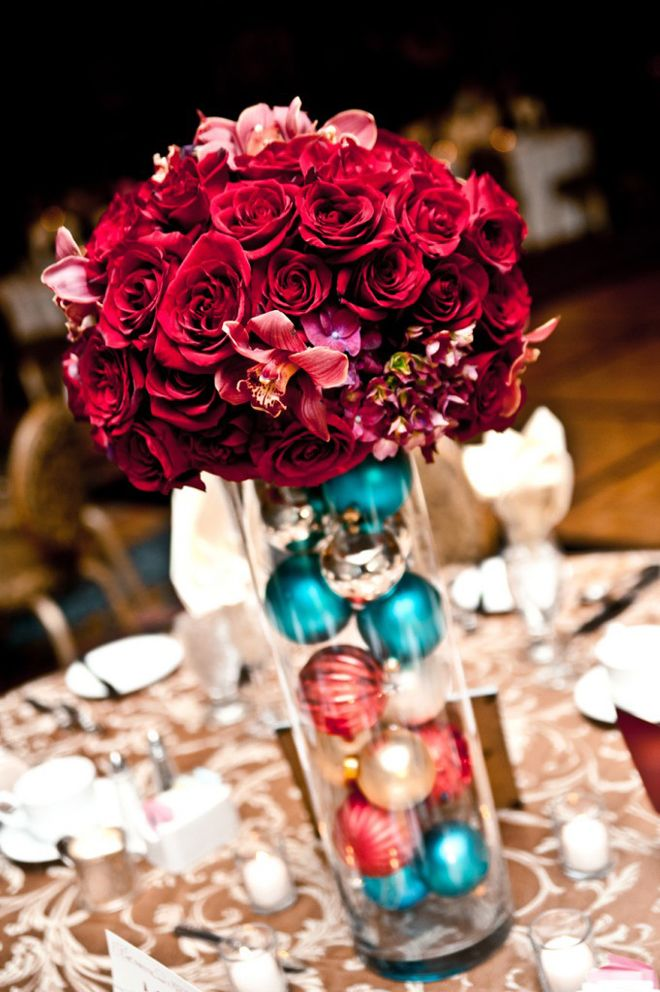 a colorful Christmas wedding centerpiece of a tall vase with colorful ornaments and bold burgundy blooms is a fun and quirky idea to try