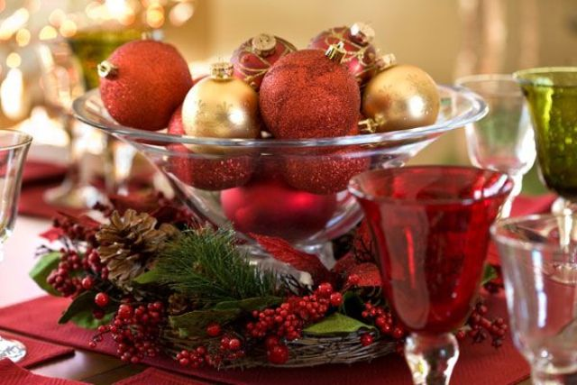 a Christmas wedding centerpiece of a glass bowl filled with burgundy and bold ornaments, with fir branches, berries and pinecones around
