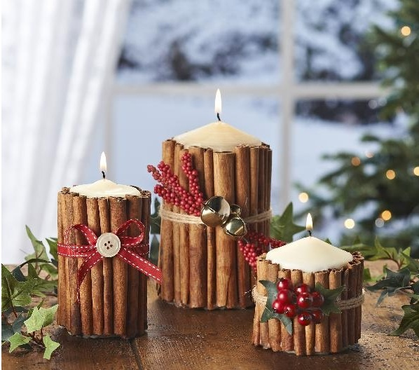 candles covered with cinnamon sticks, with faux berries, ribbons and mini bells is a very cozy and rustic idea