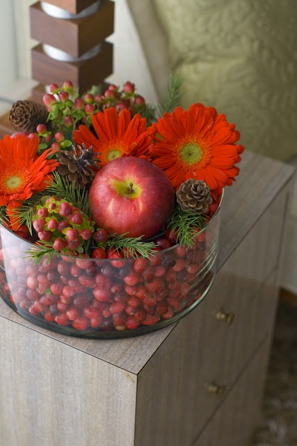 a rustic and chic Christmas wedding centerpiece of a glass bowl with berries, fir branches, red blooms, apples is a cozy idea for a farmhouse wedding