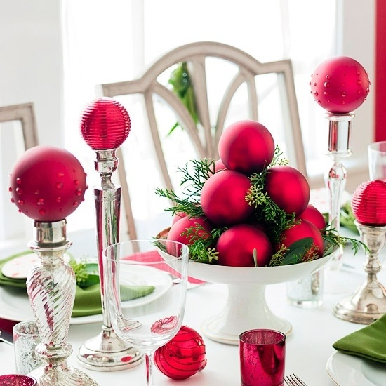 a bold Christmas wedding centerpiece of a stand with fir branches, red ornaments and tall stands with red ornaments