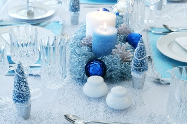 a blue Christmas wedding centerpiece of a frozen wreath with blue ornaments, candles, mini fir trees and sparkles all around