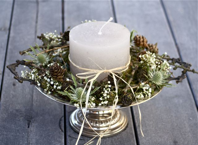 a chic rustic Christmas wedding centerpiece of a metallic stand with greenery, moss, thistles, pinecones and a candle in the center is a very cozy farmhouse piece