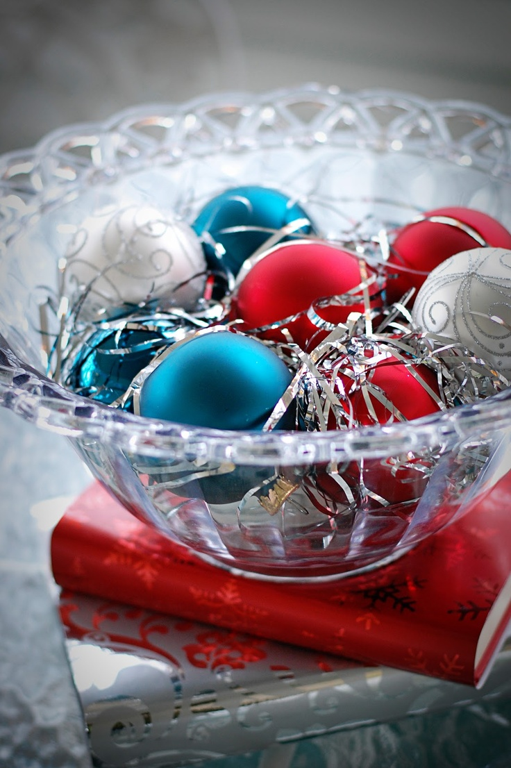 a colorful Christmas wedding centerpiece of a glass bowl with blue, red and silver Christmas ornaments is a cool idea to rock