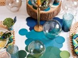 a bright blue, green, yellow, tan paper circles, succulents and moss, peacock feathers, a wood slice and yellow candles in gold candlesticks