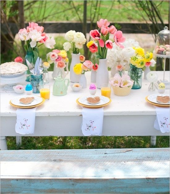 a bright and pastel wedding tablescape with white, pink, yellow blooms, blue vases, floral napkins is a fun and pretty idea for a spring wedding