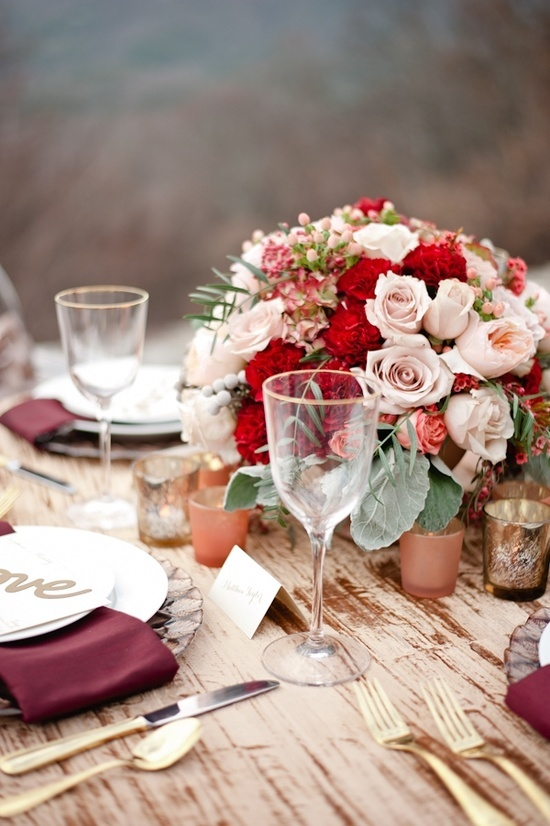 a refined fall wedding tablescape with pink and red roses, pale leaves, burgundy napkins, candleholders and gold cutlery is very chic