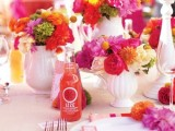 a bold summer wedding tablescape with red, hot pink, orange and yellow blooms, colorful napkins, bold drinks is a fun and cheerful idea
