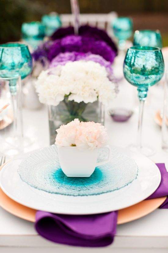 a bright wedding tablescape with turquoise glasses and glass plates, white, lilac and purple blooms, purple napkins and white roses is chic