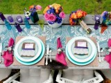 a colorful wedding table setting with a blue printed table runner, pink napkins, blue plates, bold blooms, vases and bottles