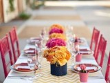 a bright tablescape with pink chairs, pink plates and tulips, a yellow chavron runner, vases with yellow and hot pink blooms