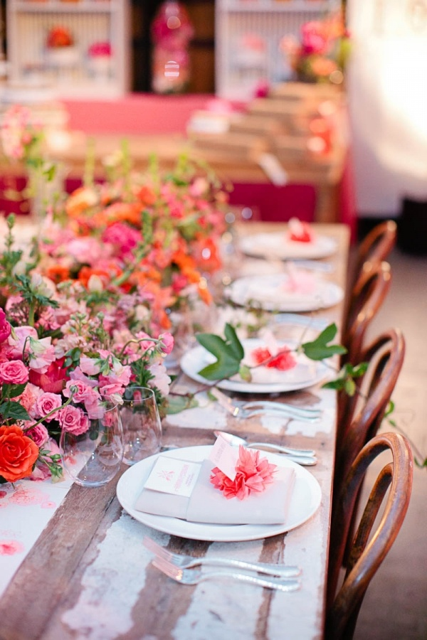 a colorful wedding tablescape with pink, orange and red blooms and greenery, neutral napkins and red blooms and greenery is a lovely idea