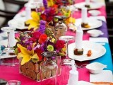 a jewel-tone wedding tablescape with a pink runner, colorful placemats, bold red, hot pink, yellow, green and purple blooms, candles and simple cutlery