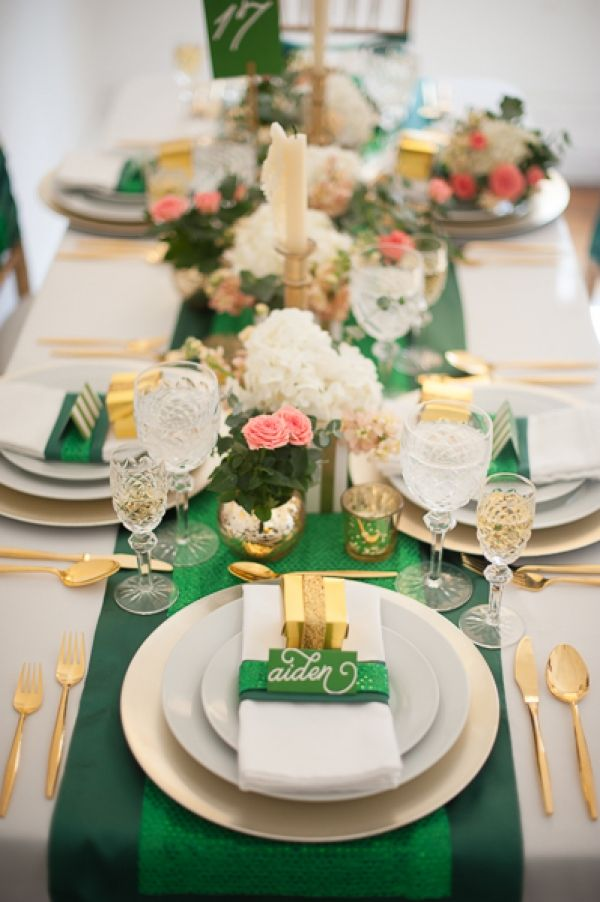 a bright and elegant wedding tablescape with an emerald table runner, napkin rings and cards, with gold favors and cutlery, pink and white blooms and foliage