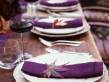a bold and chic fall wedding tablescape with purple napkins, a table runner and purple candles, fall leaves marking each place setting is amazing