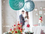 a bright wedding tablescape with green glitter plates, bold red and orange blooms and greenery, turquoise and navy yarn balls over the table