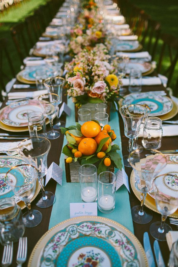 a bright wedding tablescape with a blue table runner and patterned plates, pink and yellow blooms and greenery, citrus in a box and candles is cool