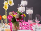 a hot pink place setting with a yellow napkin, hot pink and yellow blooms and candles in tall candleholders plus a floral tablecloth