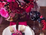 a colorful and juicy wedding tablescape with a super bold red, pink, hot pink and burgundy blooms, a fuchsia napkin and a bow, a gold goblet and gold cutlery for a wow look