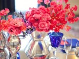 a bright wedding tablescape with hot pink and red blooms, an electric blue napkin and glasses, clear plates and mercury glass vases is amazing