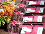 a bright tropical wedding tablescape with pink table runners, napkins and blooms, with a centerpiece of tropical fruit and flowers