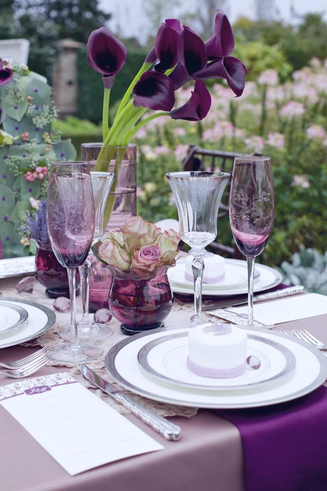 a bold wedding tablescape with a lilac tablecloth, purple napkins, purple glasses and callas, some crystals and a doily
