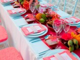 a bold tropical wedding tablescape with a blue tablecloth and plates, blue and coral chairs, a coral table runner and napkins, fruit centerpieces