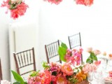 a bright wedding tablescape with pink, peachy and blush blooms and greenery, pink favors, pink blooms over the table is a beautiful idea for summer