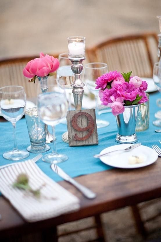 a pretty bright wedding table setting with a blue table runner, pink and hot pink blooms, candles and white porcelain and napkins