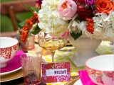 a colorful wedding tablescape with a yellow printed runner, pink napkins, floral mugs, white, pink, hot pink and orange blooms is amazing