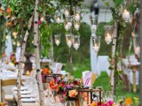a rustic wedding tablescape with super bold blooms and greenery, candle lanterns, white porcelain and napkins, hanging candleholders and greenery over the table