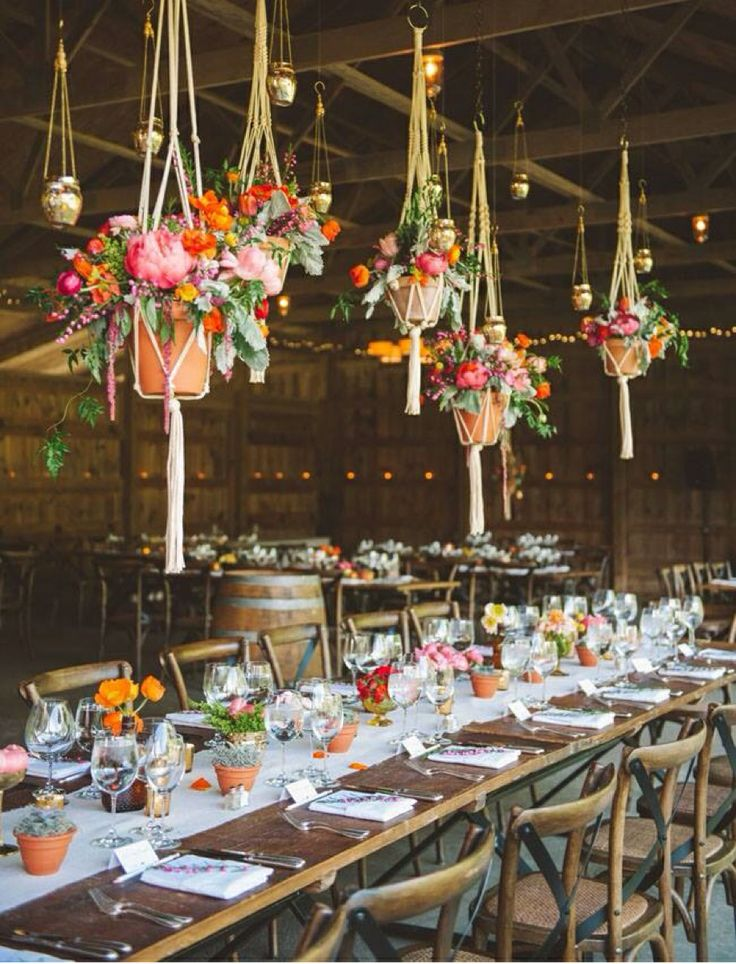 a pretty boho wedding tablescape with super bright blooms, red, orange and pink ones, greenery and succulents and hanging arrangements over the table