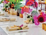 a colorful tropical wedding table setting with super bold blooms and greenery, corals, bold blooms accenting the napkins and succulents is wow