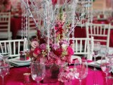 a hot pink wedding tablescape with a bold tablecloth, ribbons, hot pink and pink blooms and silver branches with crystals hanging down