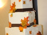a square fall wedding cake with chocolate ribbons, patterns and fall leaves plus a monogram on top