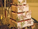 a large square fall wedding cake with burgundy and green ribbons and fall leaf decor all over the cake