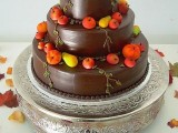 a chocolate wedding cake topped with sugar apples and pears in bright fall colors
